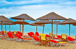 Empty sun beds with umbrellas on the beach Stock Images