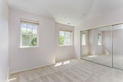 Empty sun filled bedroom with carpet floor. stock photos
