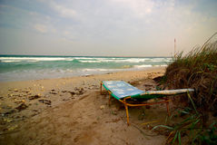 Empty sun lounger near stormy sea at windy weather Royalty Free Stock Photos