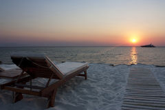 Empty sun lounger at sunset on beach with boat Stock Photo