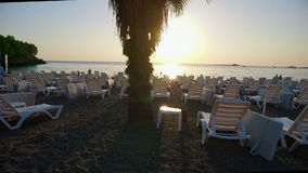 Empty sun loungers on the beach in Turkey. At sunset stock footage