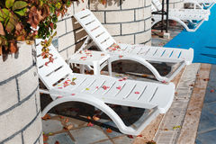 Empty sun loungers at the hotel with fallen leaves Stock Photography