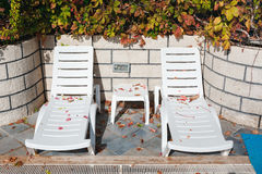 Empty sun loungers at the hotel with fallen leaves Royalty Free Stock Photography