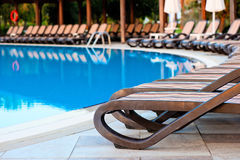 Empty sun loungers for sunbathing and swimming pool Royalty Free Stock Photos