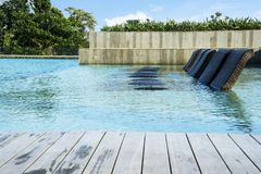 Empty sun loungers in the swimming pool royalty free stock photo