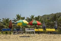 Empty sun loungers under the multi-colored beach umbrellas on the yellow sand against the green palm trees under a clear blue sky stock images