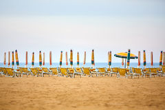 Empty sun lounges and closed parasols on the beach Royalty Free Stock Images