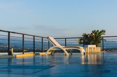 Empty Sunbed On The Rooftop Of Hotel. With palms on background Royalty Free Stock Image