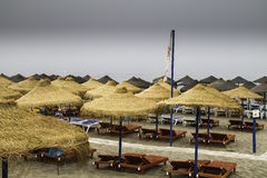 Empty sunbed and thatched umbrellas out of season in a solitary Royalty Free Stock Photography
