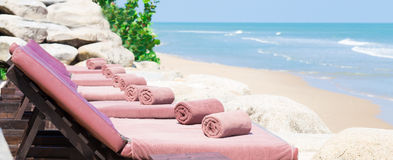 Empty sunbed with wrapped towels on a beautiful beach Stock Photography