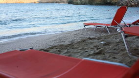 Empty sunbeds on a beach. Empty sunbeds standing on a beach by a blue sea stock footage