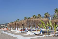 Empty sunbeds and gazebos with salt roofs on the beach in Turkey Royalty Free Stock Photo