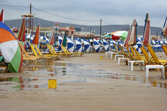 Empty sunbeds and parsaols on a beach in Crete during a cold summer shower. Everyone has fled to the shops, bars and restaurants for shelter Royalty Free Stock Photos