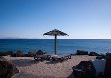 Empty sunbeds in playa blanca. Overlooking fuerteventura Royalty Free Stock Photography