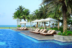 Empty sunbeds by the resort pool Royalty Free Stock Photography