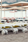 Empty sunbeds on the sand beach at a sunset Stock Photo