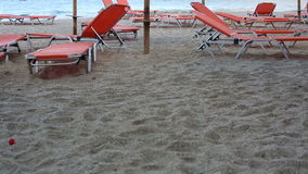 Empty sunbeds standing on a beach by a blue sea stock video