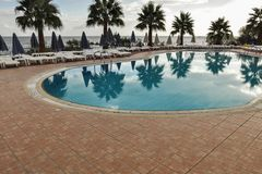 Empty sunbeds and swimming pools with palms around. stock image