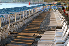 Empty sunbeds and umbrellas on a hotel beach Stock Images
