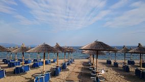 Empty sunbeds and umbrellas sandy beach and blue water sea Royalty Free Stock Image