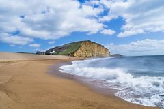 Empty sunny beach at West Bay in Dorset. Sunny beach at West Bay in Dorset with crashing waves and Jurassic Coast cliffs in background Stock Photography