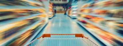 Empty supermarket aisle, motion blur. Shopping cart with empty supermarket aisle, motion blur Royalty Free Stock Image