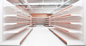 Empty supermarket aisle. Perspective view of a shopping aisle with empty shelves in motion blur royalty free stock photo