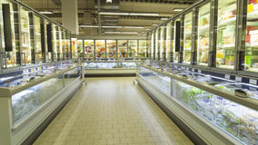 Empty supermarket aisle with shelves full of products Stock Photo