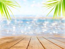 Empty surface of a wooden table on a background of beach and palm leaves. royalty free stock photos