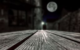 Empty surface of a wooden table in a village with a mysterious figure of a man at night royalty free stock photography