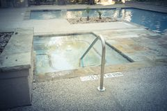 Empty swimming pool and Jacuzzi tubs at apartment living in Texas, USA. Swimming pool and Jacuzzi tubs with handrail and depth signs at apartment building in stock photo