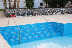 Empty swimming pool with metal ladder. Stock Images