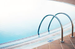 Empty swimming pool silver handles in holiday resort. Royalty Free Stock Images
