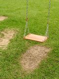 Empty swing - 1. Empty wooden swing in a green park, distant view Royalty Free Stock Photo