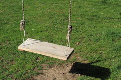 Empty swing. With the grass behind royalty free stock images