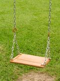 Empty swing - 2. Empty wooden swing in a green park, close-up view stock photo