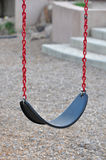 Empty Swing. A single empty child swing with red chains and a black seat against a neutral background Stock Photo