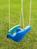 Empty swing - 3. Empty plastic swing in a green park, close-up view from behind stock photo