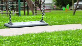 Empty swing with chains swaying at playground for child, moved from wind, on green meadow background stock video