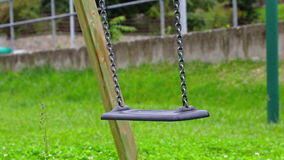 Empty swing with chains swaying at playground for child, moved from wind, on green meadow background stock footage