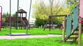 Empty swing with chains swaying at playground for child, moved from wind, on green meadow background in slow motion loopable
