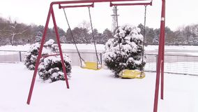 Empty swing chairs. Two empty swing chairs oscillating in a park with winter scenery stock video