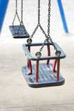 Empty swing on children playground in city. Stock Photos
