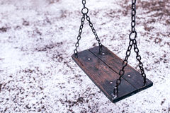 Empty swing on children playground under snow Stock Images