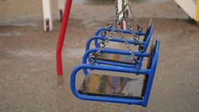 Empty swing drenches in the rain, swaying in wind. a heavy rain, a thunderstorm, a downpour with a strong wind. In yard. There is a children`s playground with stock video footage