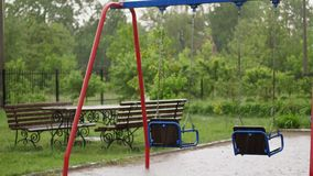 Empty swing drenches in the rain, swaying in wind. a heavy rain, a thunderstorm, a downpour with a strong wind. Swing on. Empty swing drenches in the rain stock video footage