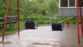 Empty swing drenches in the rain, swaying in wind. a heavy rain, a thunderstorm, a downpour with a strong wind. In yard. There is a children`s playground with stock video