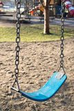 Empty swing in kids playground. Closeup of an empty swing in kids playground in urban environment Royalty Free Stock Images