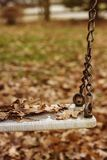 Empty swing with leaves in the autumn season Royalty Free Stock Photo