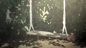Empty swing in motion stock footage